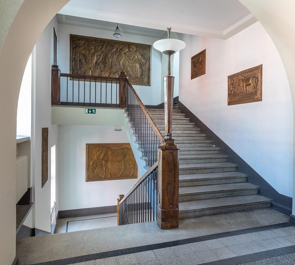 Avara porraskäytävä, rappuja ylös ja alas, seinillä taideteoksia.