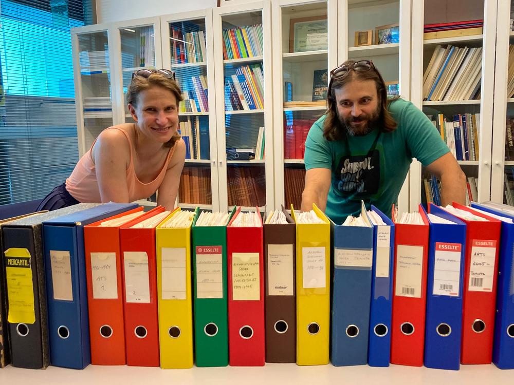 Jenni Savonen ja Teemu Kaskela seisovat värikkäiden mappien takana.