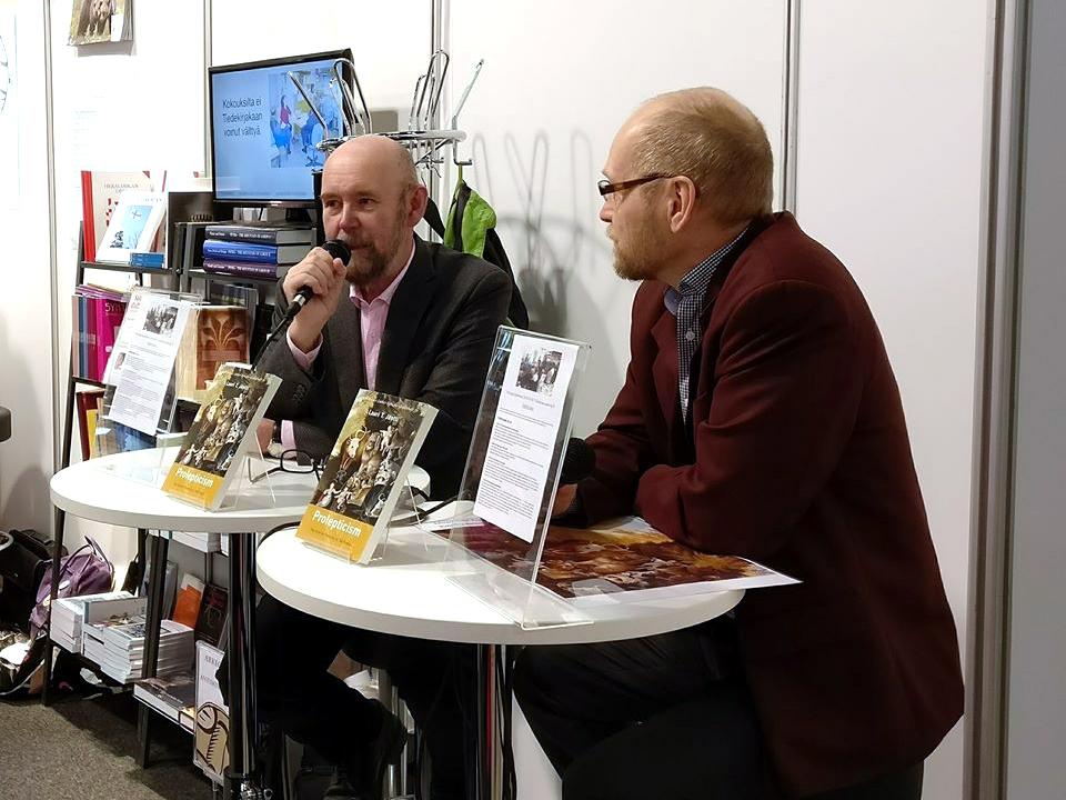 Esko Valtaoja haastattelee Lauri T. Jänttiä pöydän ääressä kirjamessuilla.