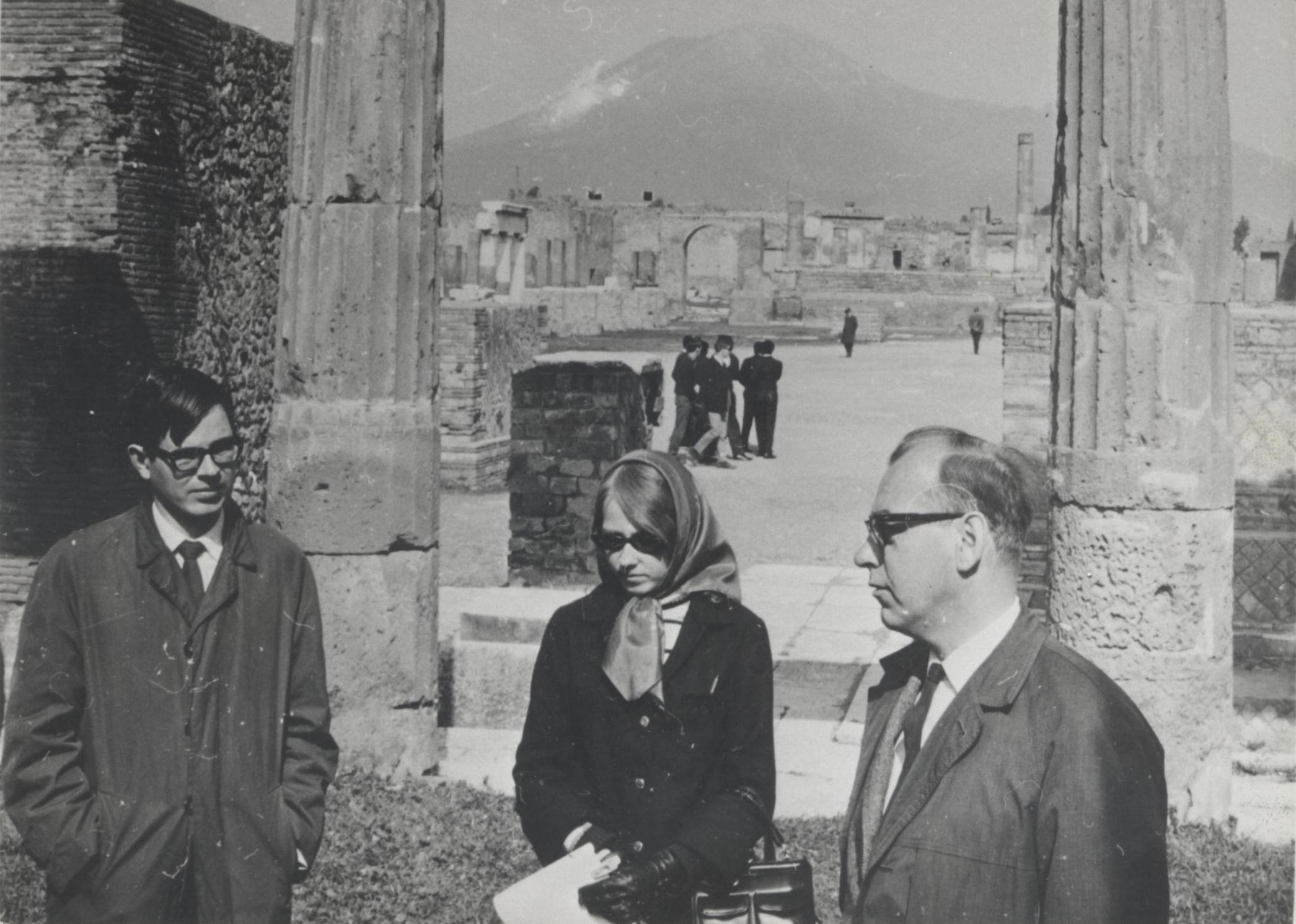 Svartvit bild på professor Patrick Bruun (till höger) med två studenter. I bakgrunden syns antika pelare och andra stadsruiner.
