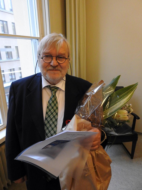 Voittaja Seppo Hentilä kukkien kanssa.