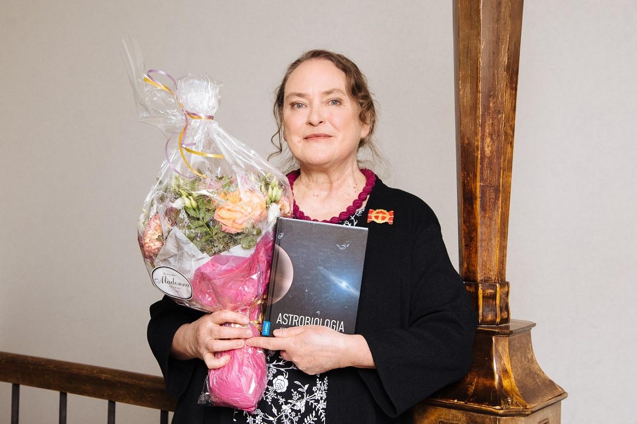 Kirsi Lehto sylissään palkintokukkia ja kirja Astrobiologia.