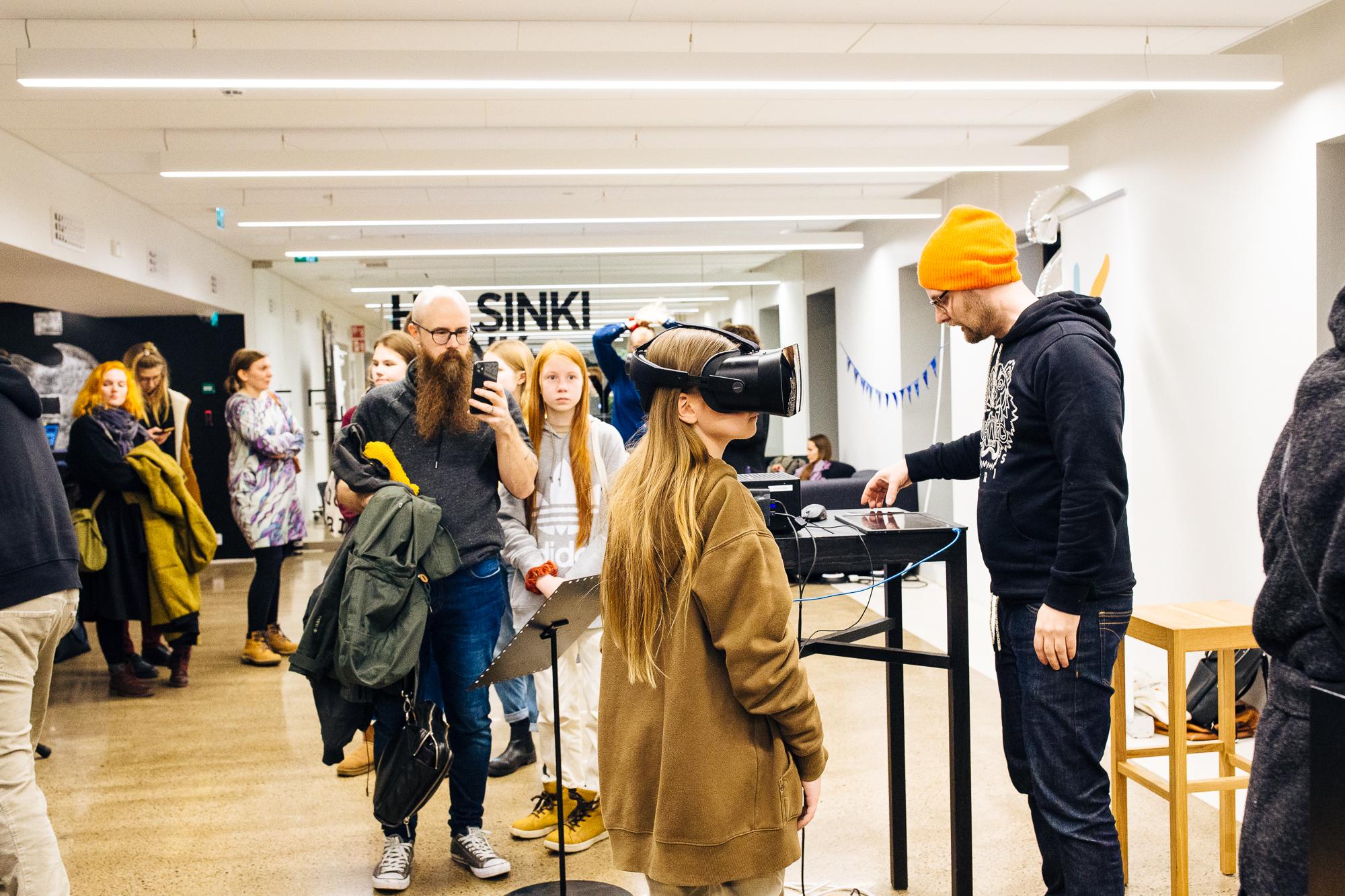 Tiedetapahtuma, jossa yleisö saa kokeilla 3D-laseja, nuorella lasit päässä, muut odottavat vuoroaan.