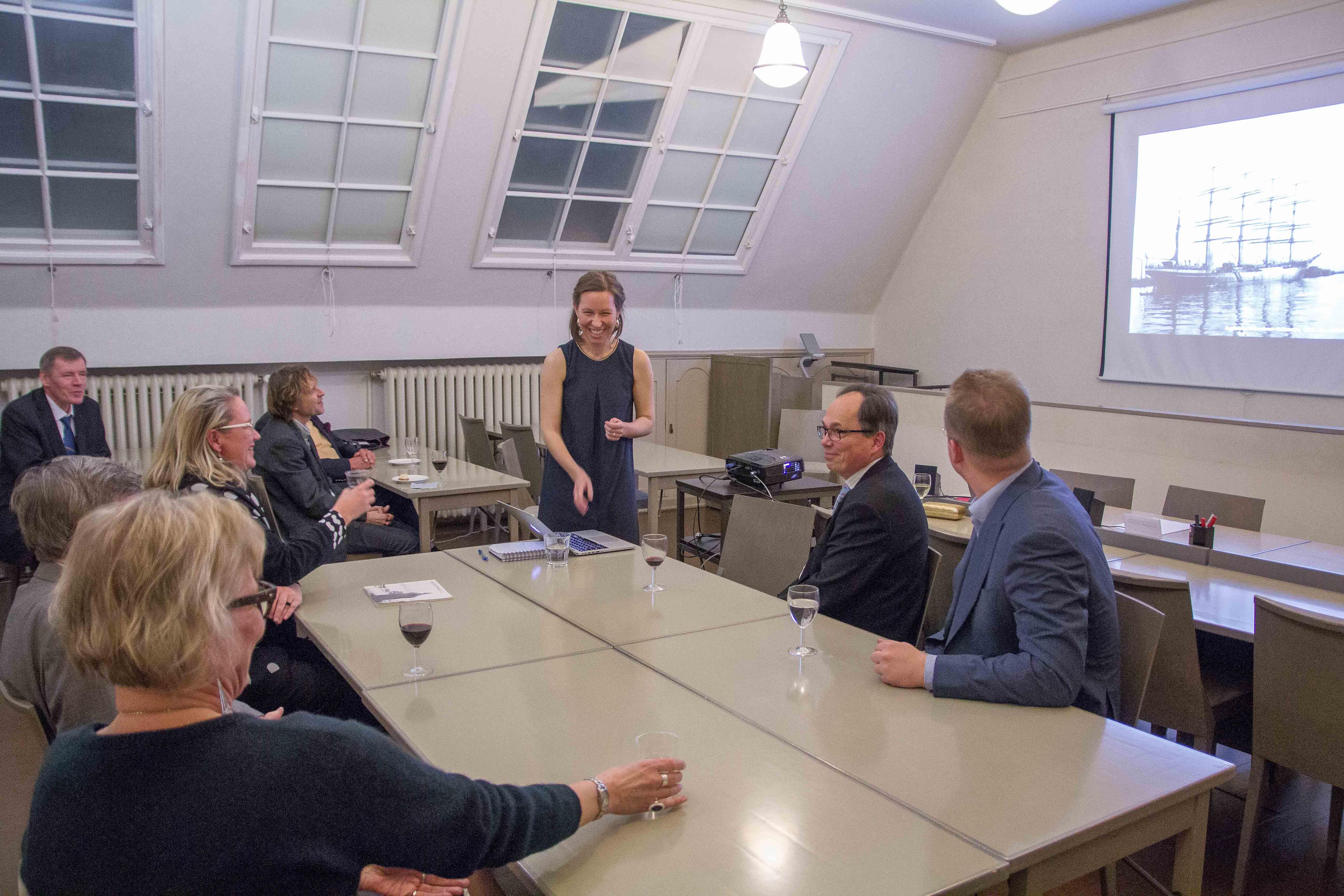 Ihmiset pöydän ääressä osallistuvat paneelikeskusteluun merihistorian nykyisyydestä ja tulevaisuudesta.
