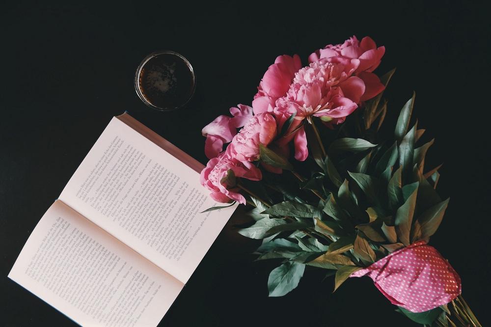 En öppen bok och en blombukett på ett bord.