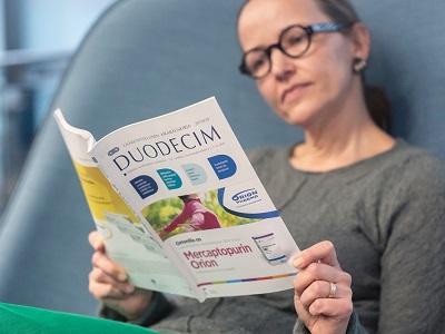 Henkilö lukee Duodecim-lehteä.