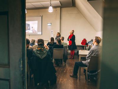 Genom dörröppningen syns åhörare som följer en presentation.