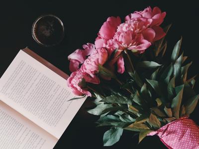 Artikkelin kuvituskuva. Pöydällä kirja ja kukkakimppu.