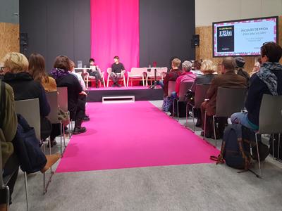 Yleisöä lavan edessä. Lavalla on kaksi keskustelijaa.