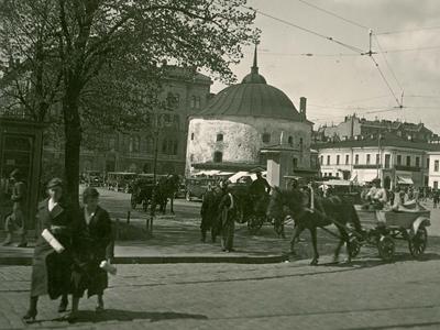 Människor och hästvagnar på torget. En rund, vit byggnad syns i bakgrunden.