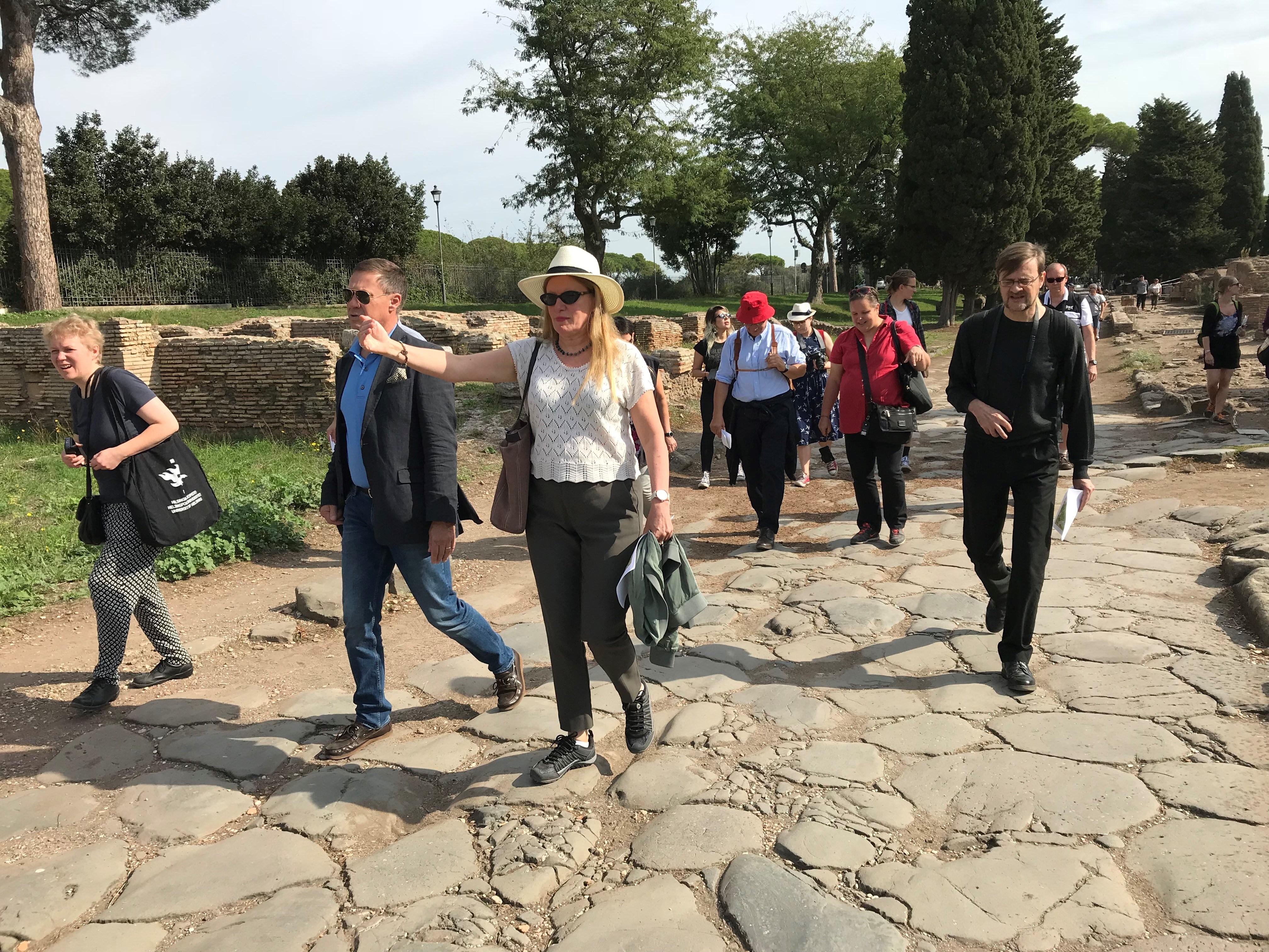 Människor promenerar på en väg av stenar invid ruiner.