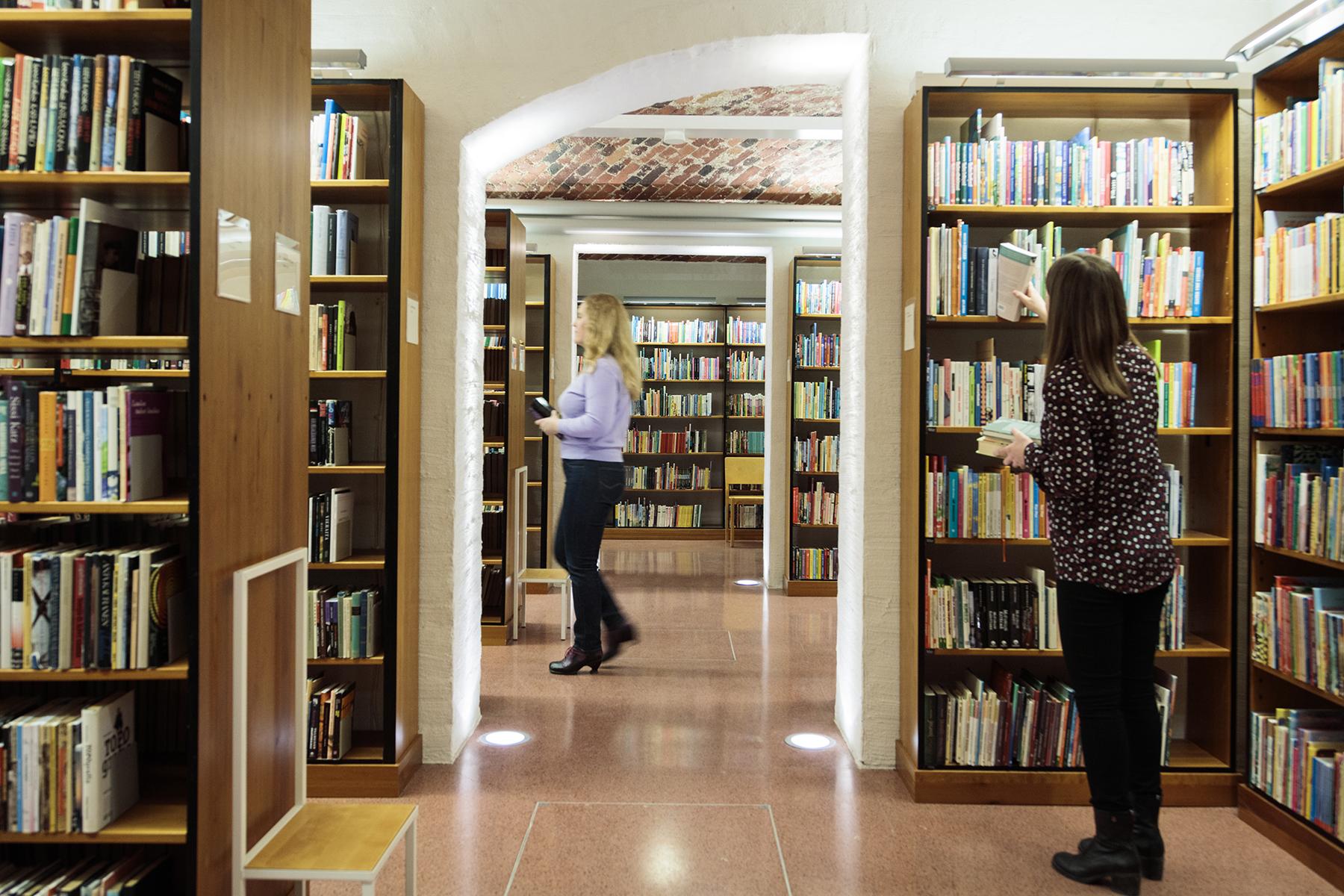 Två personer bland bokhyllor.