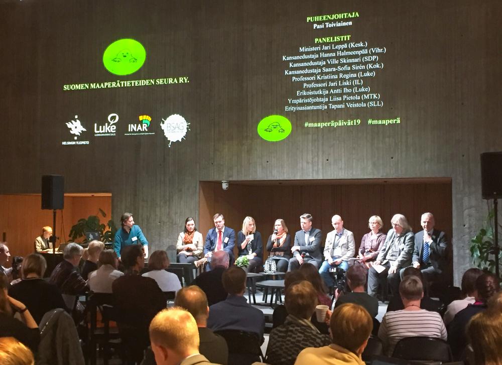Nio personer sitter i en rad på en scen framför en publik.