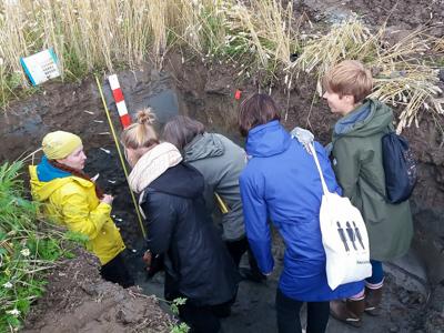 Viisi ihmistä seisovat maakuopassa tutkien Liedon savimaaprofiilia.