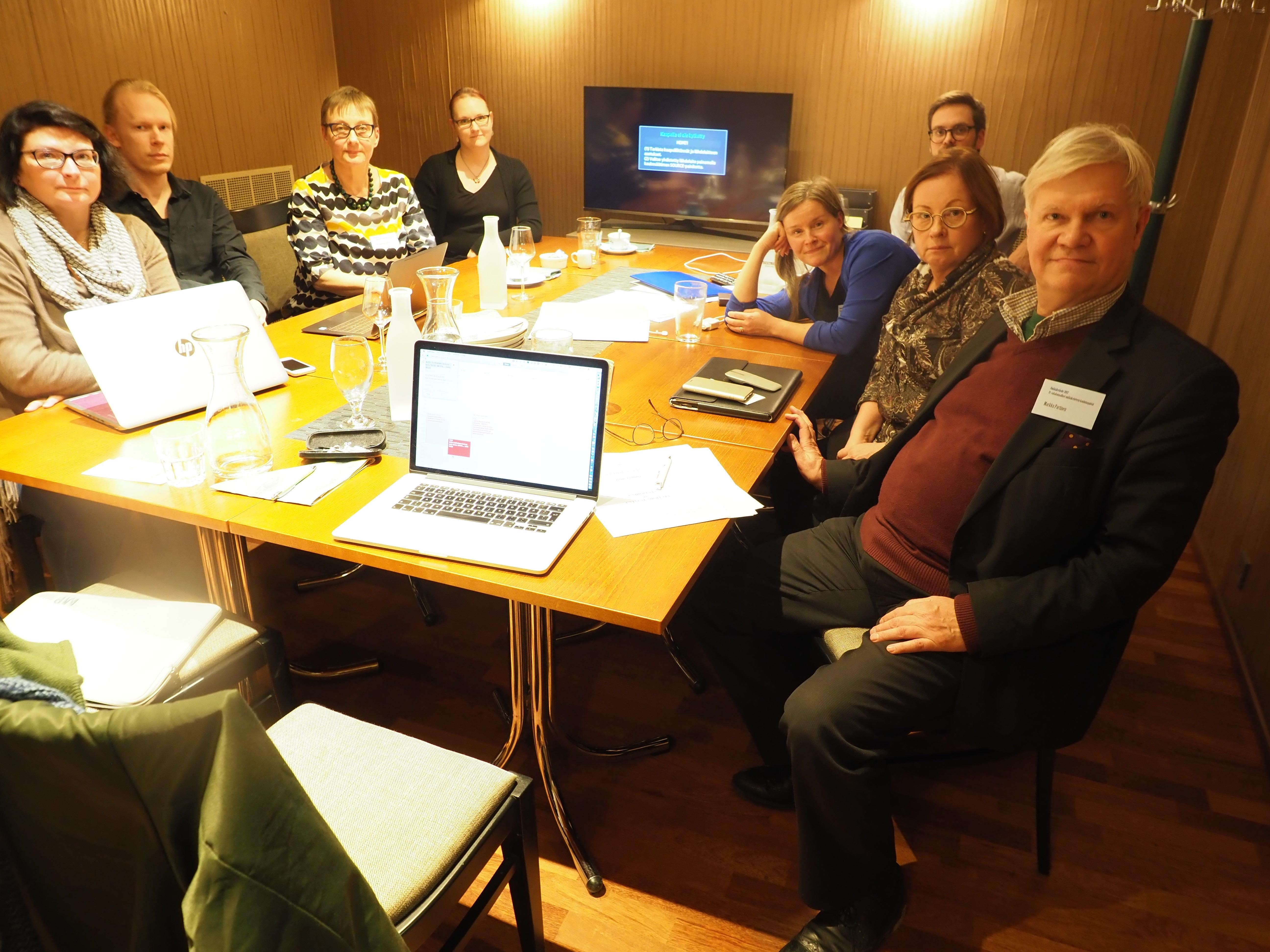 Styrelsemedlemmarna sitter runt ett bord och tittar mot kameran.