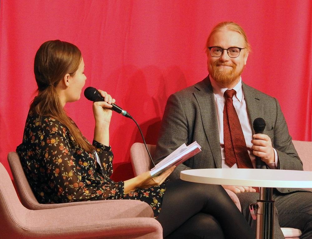 Kaksi henkilöä keskustelee lavalla mikit käsissään.