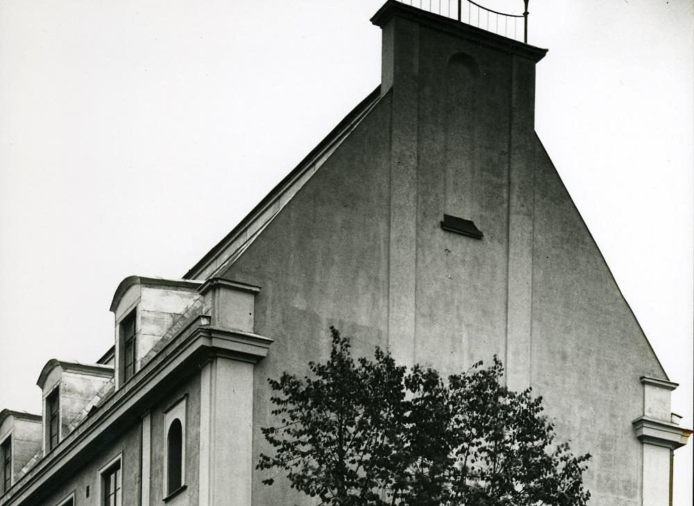 Mustavalkoinen kuva ison talon päädystä, josta kohoaa harja korkealle vasten taivasta.