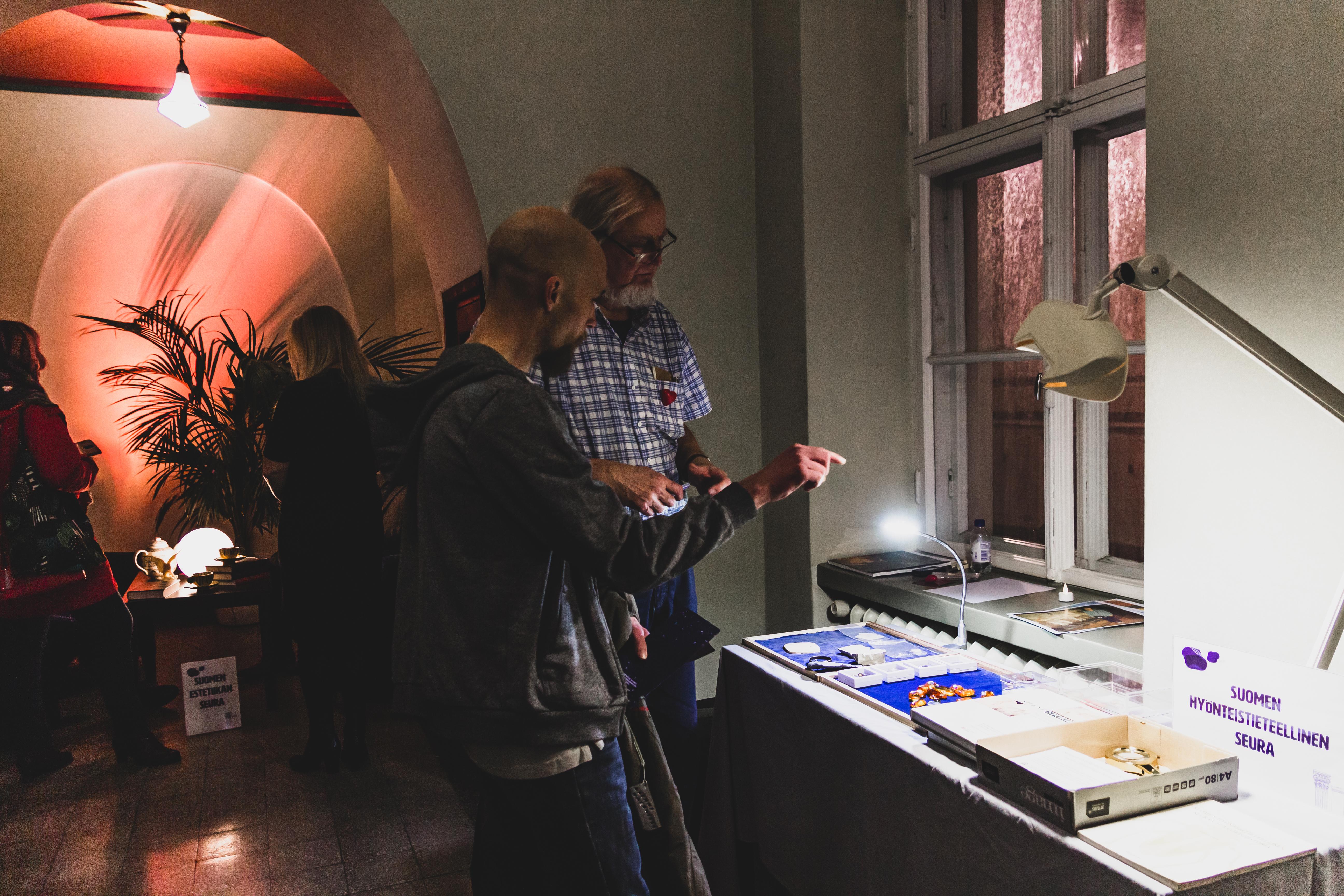 Tunnelmallinen kuva Tieteiden yöstä, muutama ihminen tarkastelee näyttelypöytää.