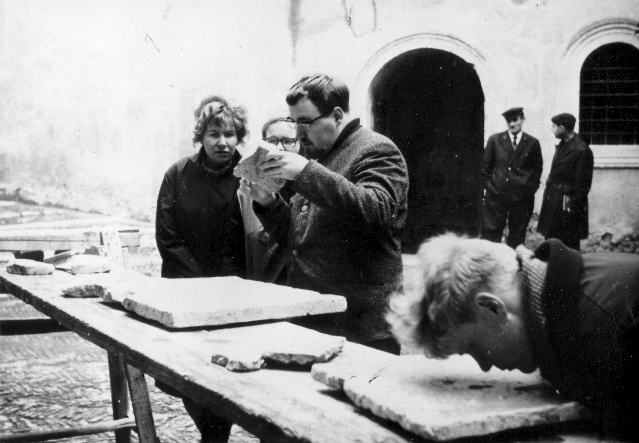 Svartvit bild. Fyra personer undersöker tegelplattor.