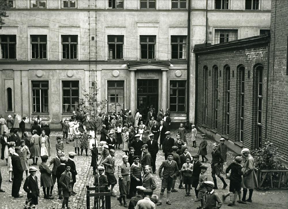Historiallinen mustavalkoinen kuva, lapsia leikkimässä koulun sisäpihalla.
