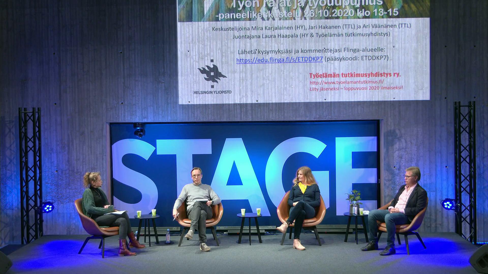 Fyra personer sitter på stolar på en scen.